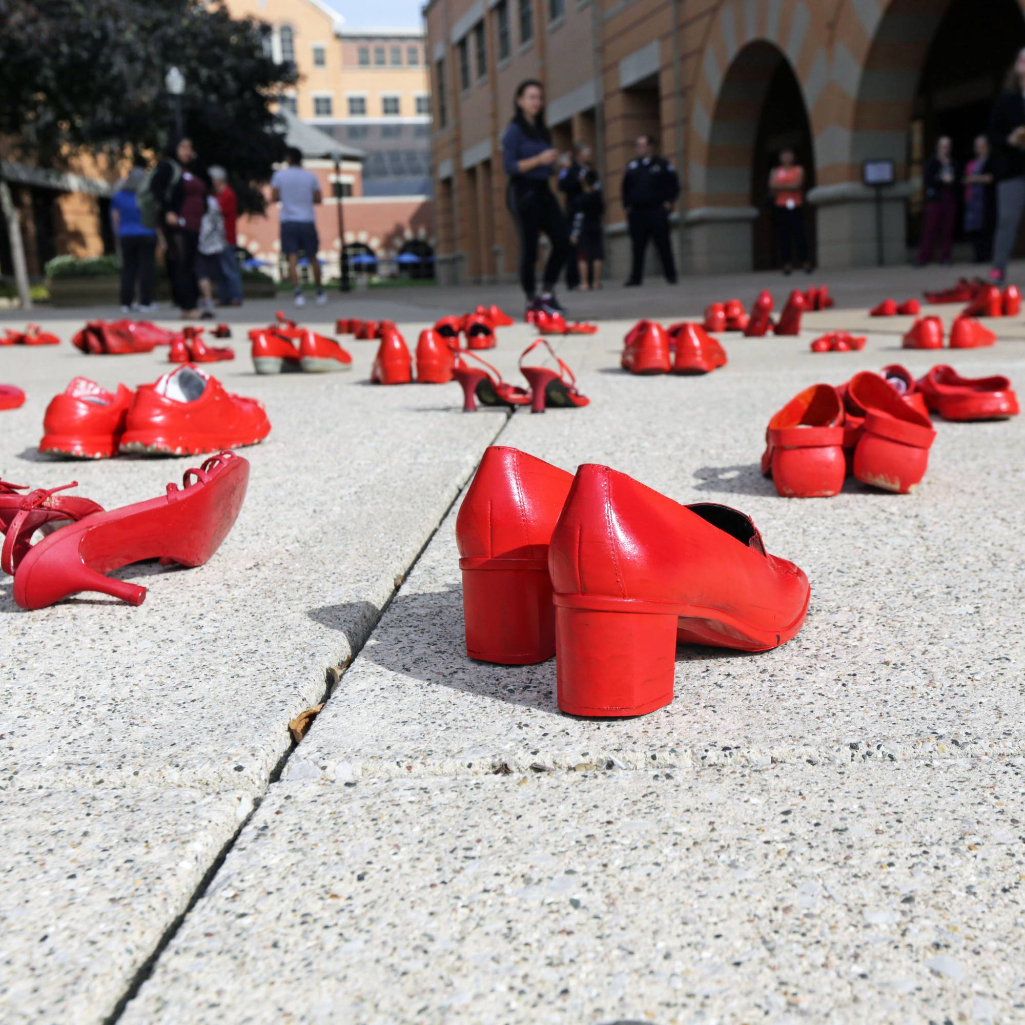 pairs of red shoes arranged across brick courtyard